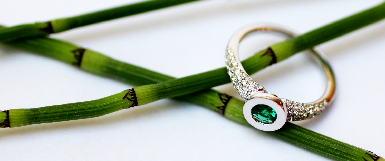 Cette bague de fiançailles originale, dans un style contemporain, avec émeraude et diamants est un bijou sur mesure. La joaillerie sur mesure est la spécialité de la créatrice de bijoux, Annette Girardon.