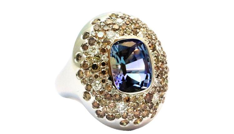 Cette bague boule en or blanc est une création de bijoux sur mesure. Elle est sertie d'une tanzanite au centre, entourée d'un pavage de diamants blancs et bruns. made in Paris
