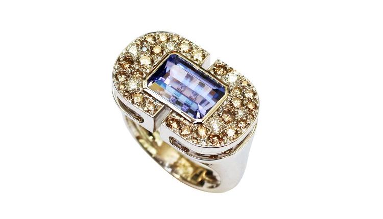 Une bague joaillerie en or blanc, sertie de diamants bruns et blancs et d'une tanzanite taille éméraude, a été créé par un joaillier à Paris, Annette Girardon.