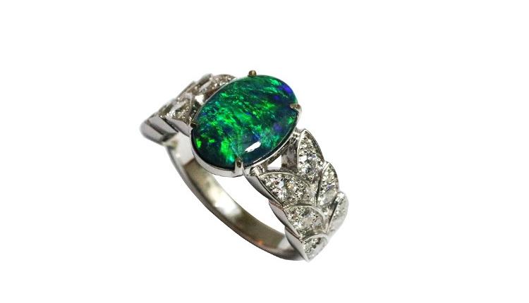 Une belle opale noire d'Australie est sertie sur cette bague sur mesure paris originale par des feuilles en or blanc, serties de brillants.