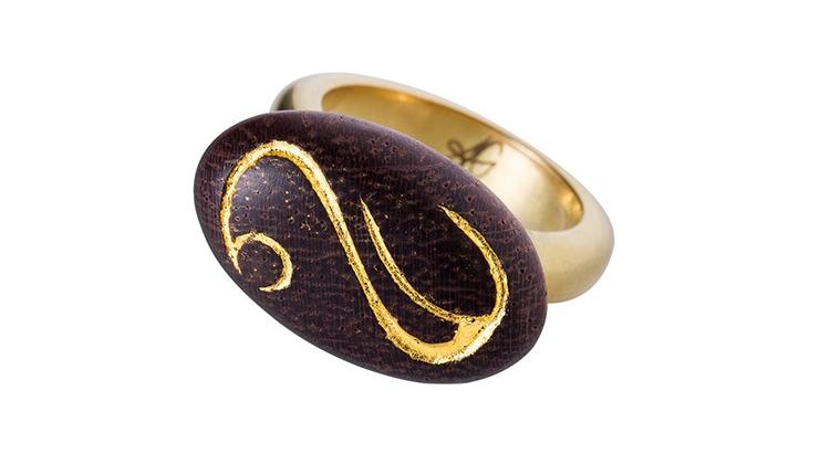 Une bague en bois exotique, or 22 carat et portant une gravure, dorée à la feuille d'or. Il s'agit d'une création de bijou rare, par Annette Girardon, installée à Paris.