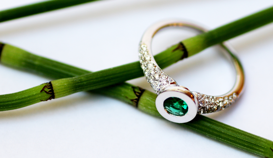 A pretty emerald adorns this engagement ring in white gold and diamonds. This original custom-made piece of jewellery, stands out from the crowd and remains timeless.