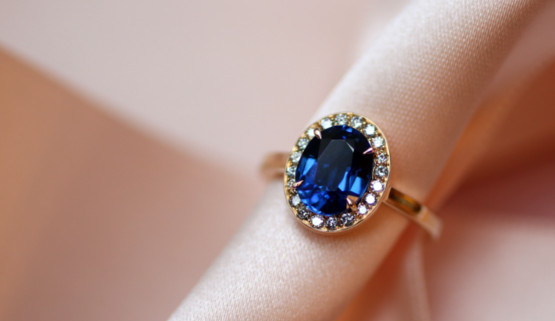 The yellow gold engagement ring, with sapphire and its diamond surround, is a vintage engagement ring in its style, with a modern side by the square shape of its body.