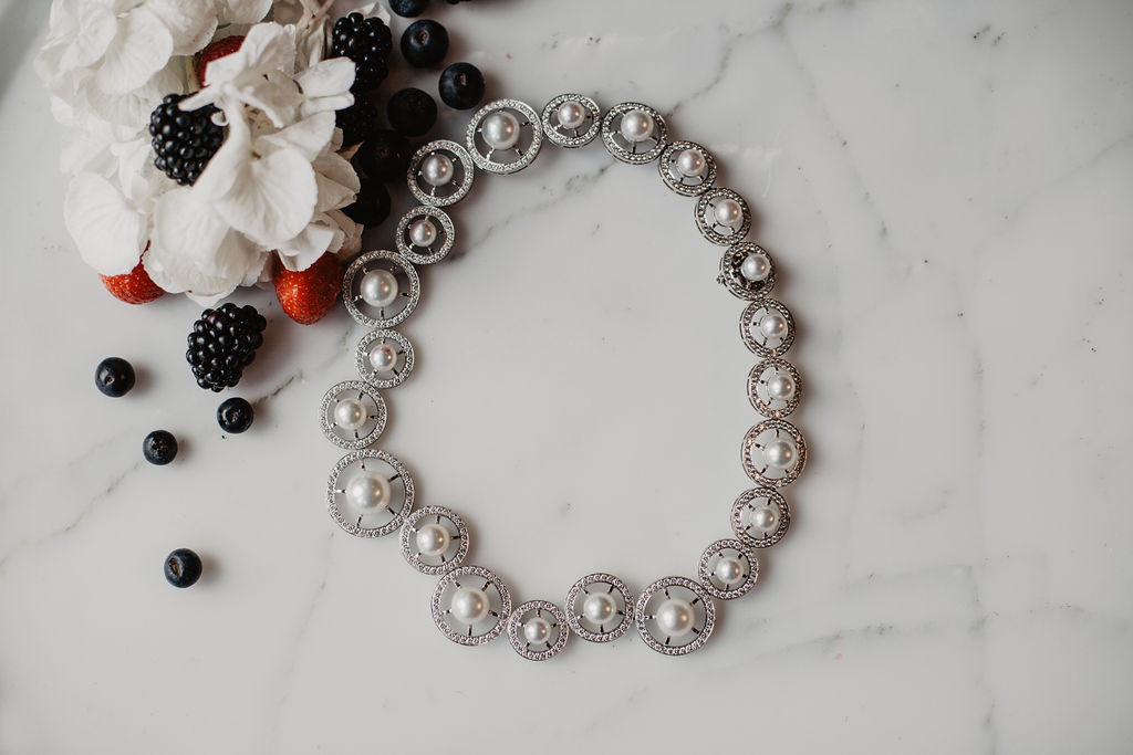 Collier formé de cercles de différentes taille enor blanc, sertis de diamant avec une perle au milieu.