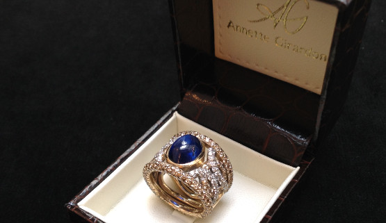 This handmade jewel  is made of champagne gold  and set with a sapphire cabochon and brown and white diamonds. It was created by Annette Girardon, in Paris.