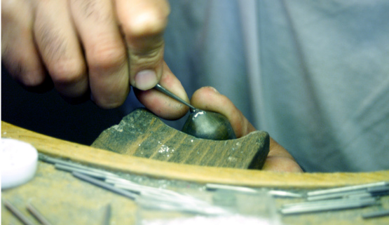 A craftsman, specialized in stone setting, Here, a stone is being set in a handcrafted jewel according to french jewelry tradition.