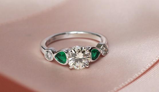 Bague de fiançailles en or blanc palladié, sertie de trois diamants rond et de deux émeraudes triangulaires.