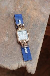 Une montre en or ancienne, qui a été montée en broche avec du lapis lazuli, par Annette Girardon, à Paris.