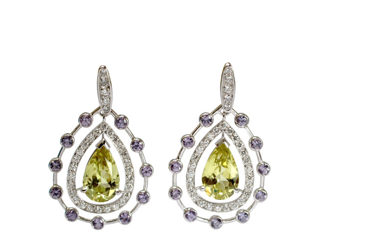 Fine jewellery earrings in pear shape and white gold with chrysoberyl in the center and diamonds and purple sapphires arround them.
