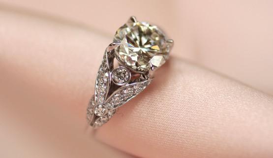 Romantischer Verlobungsring in Weissgold, mit Diamanten besetzten Blättchen neben dem Zentralstein.kleinen