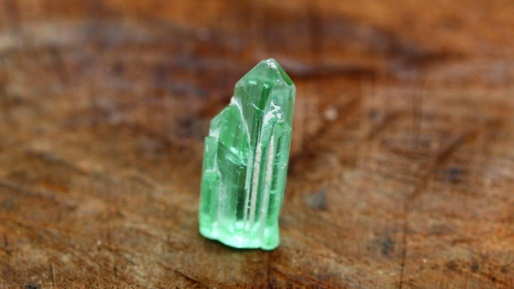 Tourmline de couleur vert d'eau non taillée, une pierre brute exposée sur un fond en bois.