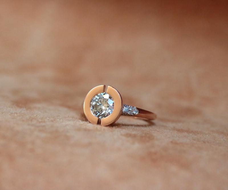 Ein Diamant ist in einer in der Mitte geöffneten Scheibe aus Rotgold gefasst. Ein Diamant Pave auf dem Körper des Rings rundet das Design ab.