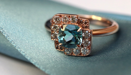 Custom made rose gold engagement ring with an aquamarine cushion, set in a square, paved with white and brown diamonds. This design is inspired by the Art Deco style.