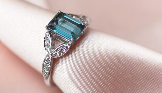 This engagement ring for women features a rectangle aquamarine of the Santa maria africana variety. The ring is made of palladium white gold and is set with diamonds on elements evoking leaves.
