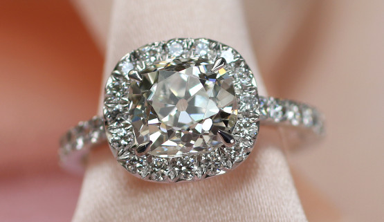 A cushion cut diamond is surrounded by brilliants on white gold. The body of this women's engagement ring is paved with brilliants.