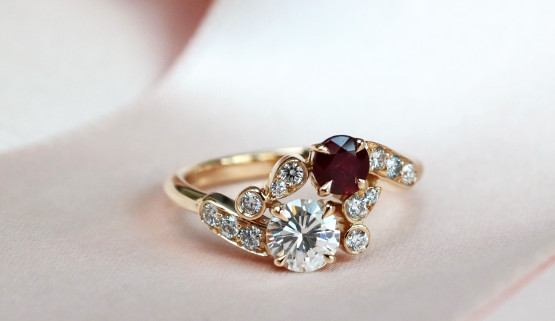 Gold engagement ring in the style of 'toi et moi' with a diamond and a ruby of smaller size, embellished with other elements set with diamonds that are arranged to evoke a floral bouquet.