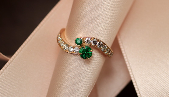 The yellow gold body of this engagement ring turns like a wave around the finger, without meeting in the middle. It is set with diamonds. On the top, there are two round emeralds, one in claw setting, the other in closed setting.