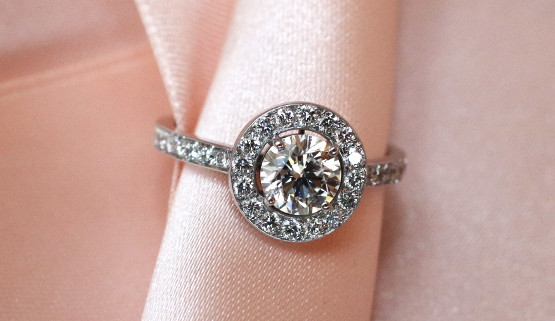 A brilliant with claw setting, is surrounded by a band of palladium white gold, set with diamonds. A small space between the central stone and the diamond in the center gives this engagement ring a clear design. The diamond paving continues on the ring body until halfway around the finger.