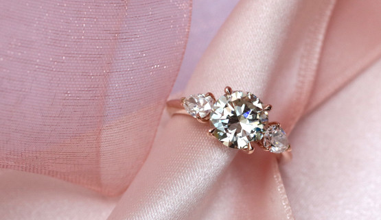 Rose gold engagement ring with a 2 carat center diamond, accompanied by two pear diamonds on each side. This ring for women was made in Paris, by the jeweler Annette Girardon .