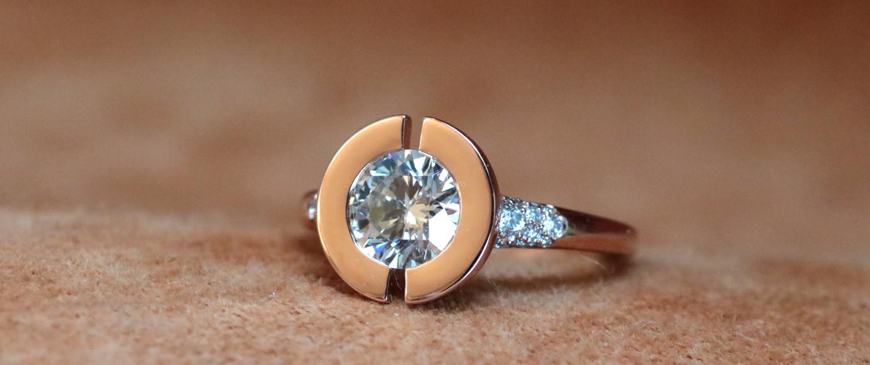 Moderner Rotgold Ring im Art Deco Stil mit einem Diamanten in einer offenen Scheibe gefasst und Diamant Pavé auf dem Ring Körper.
