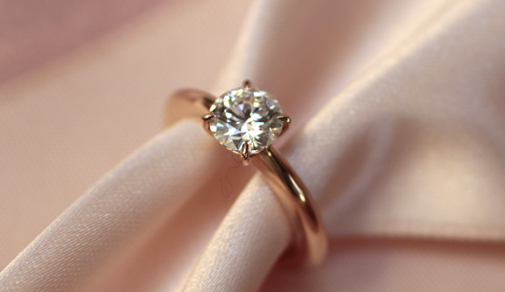 This engagement ring is a red gold solitaire set with a 0.7 carat diamond. The ring becomes thinner towards the stone. The diamond is set with 4 claws and does not protrude too much from the finger.