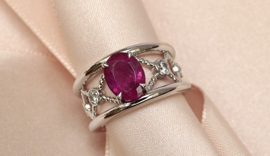 An engagement ring in the shape of a band, with an oval ruby in the center and diamonds arranged in a latticework decoration on the side and fashioned in palladium white gold.